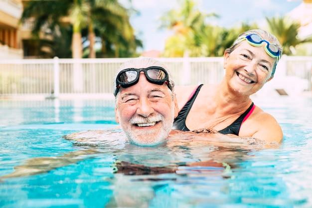 수영장 물에서 껴안은 두 노인 - 수영장에서 함께 운동하는 활동적인 남녀 - 사랑으로 포옹