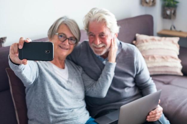 Пара из двух пожилых людей или пожилых людей на диване с ноутбуком и делает селфи с ее телефоном - кавказские старики