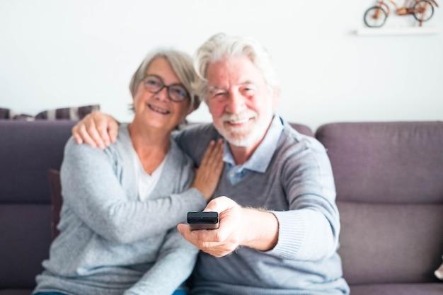 Пара из двух пожилых людей или пожилых людей вместе на диване у себя дома смотрит телевизор или какой-то фильм или сериал - мужчина держит пульт дистанционного управления, меняя канал