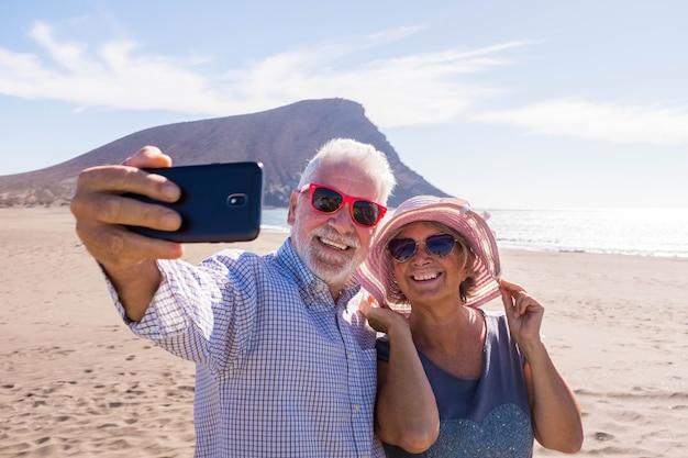 해변에서 함께 셀카를 찍는 두 노인 부부 - 행복한 성숙한 노인들이 웃고 전화 카메라를 바라보고 있다