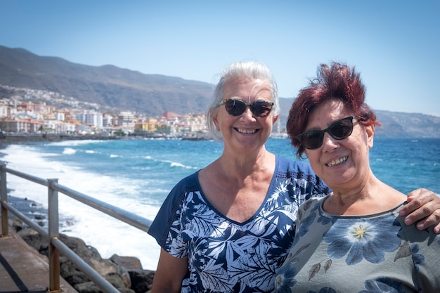 海の遠足で楽しんでいる2人の姉妹のカップル青い海と白い波の笑顔と抱擁