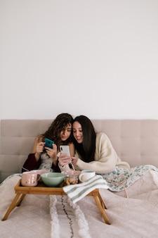 携帯電話を見ながらベッドに横たわっている黒髪の2人の白人女性のカップル。彼らは小さなテーブルで朝食を用意しています