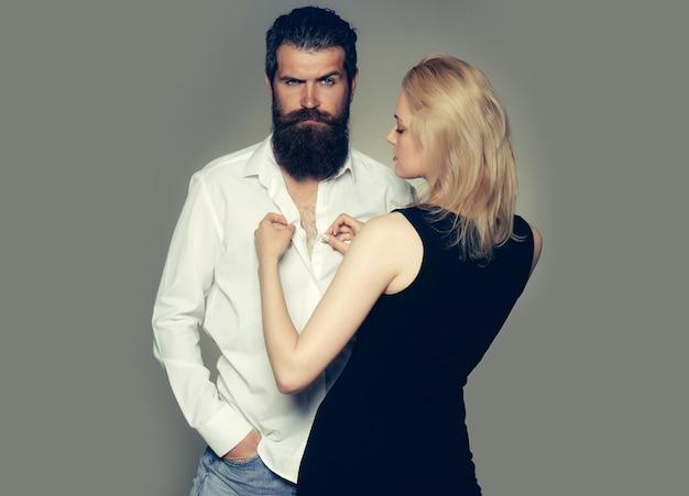灰色のスタジオで白いシャツを着た女性とハンサムなひげを生やした男のカップル