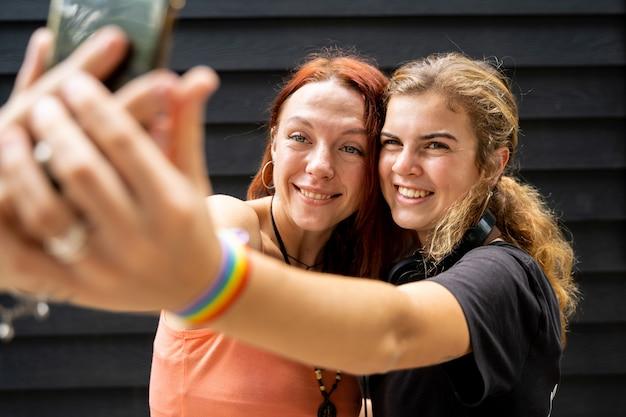 Selfieを作るlgtbフラグブレスレットを持つ女性のカップル