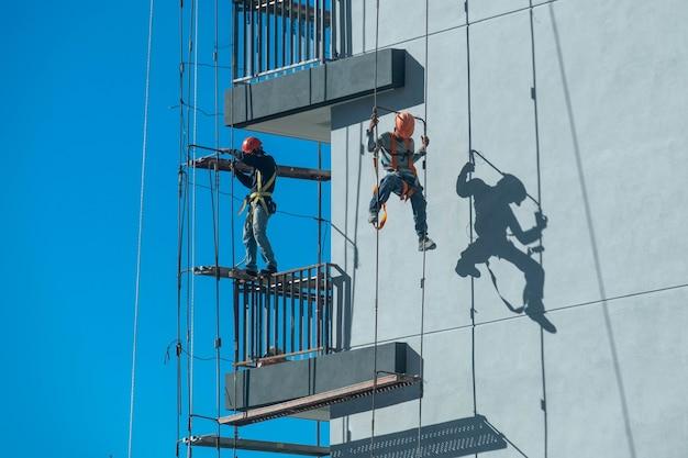 모든 안전 조치를 준수하면서 비계를 고정하고 등반하는 두 명의 작업자