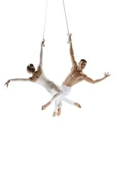完璧な白いスタジオの背景トレーニングに分離された若いアクロバットサーカスアスリートのカップル