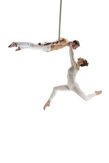 白で隔離の若いアクロバットサーカスアスリートのカップル