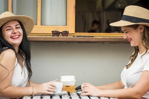 若くて幸せな白人の女の子のカップルは、屋外のバーで一緒に笑ったり、コーヒーブレイクを楽しんだりしています-友情や関係の陽気な女性は余暇を楽しんでいます
