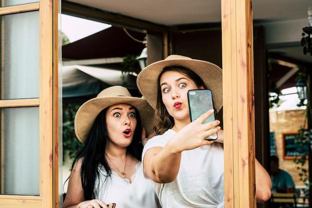 若い白人女性の友人のカップルは、面白い表現と一緒に自撮り写真を撮るのが楽しい
