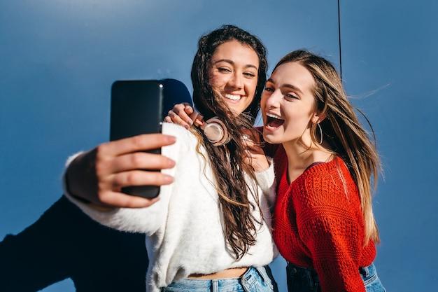 青い背景の上の携帯電話でselfieを取るブロンドの若い女の子と1つのブルネットのカップル