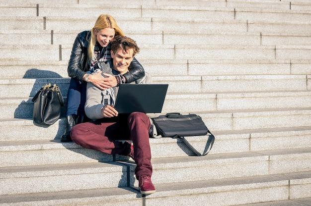 Пара молодых хипстеров с ноутбуком в городе в осенний солнечный день