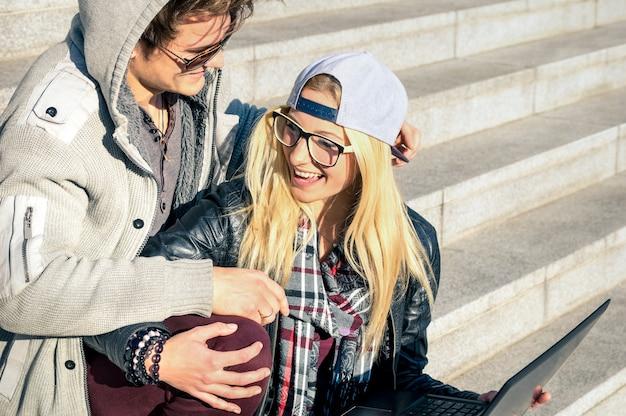 Пара молодых хипстерских людей с компьютерным ноутбуком в городе на открытом воздухе