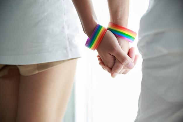 Lgbtの旗で覆われている若いレズビアンの女の子のカップルは彼女のカップルの手を握ります。