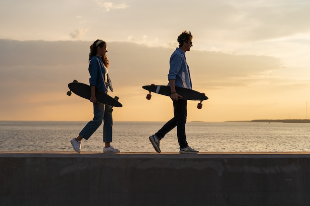 若いロングボーダーのカップルは、日没のライフスタイルと自由の概念でスケートを運ぶ海辺を歩きます