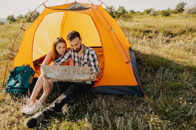 Пара молодых мужчин и женщин, сидя в палатке, глядя на бумажную карту.
