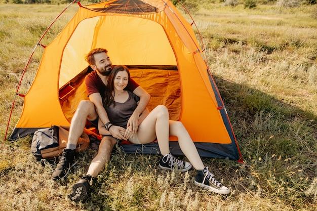 Пара молодых мужчин и женщин, сидя в оранжевой палатке в горах.
