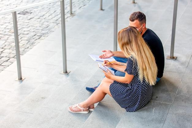 Пара молодых людей делают домашнее задание на ступеньках университетского городка