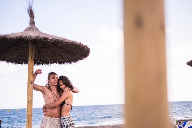 Пара молодых симпатичных мужчин и женщин обнимаются на пляже под солнцем под зонтиком