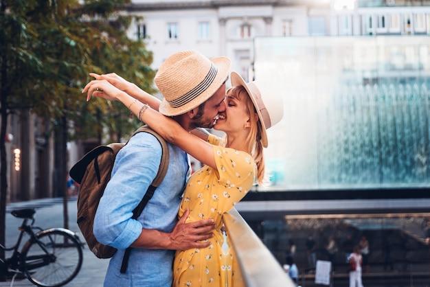 Пара молодых влюбленных туристов, имеющих романтический поцелуй в городе