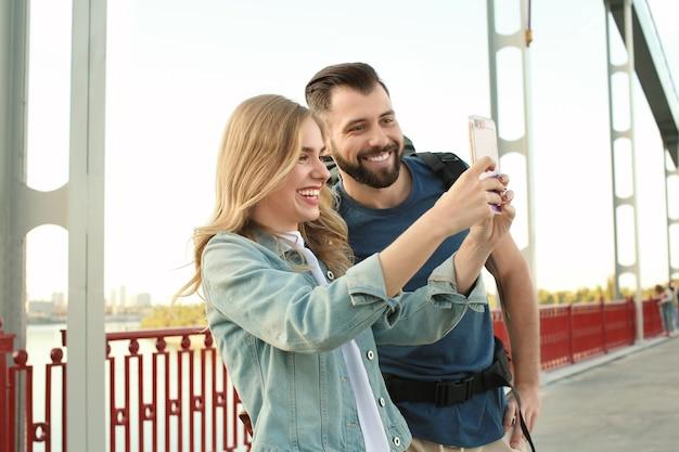 다리에 사진을 복용하는 젊은 관광객의 커플