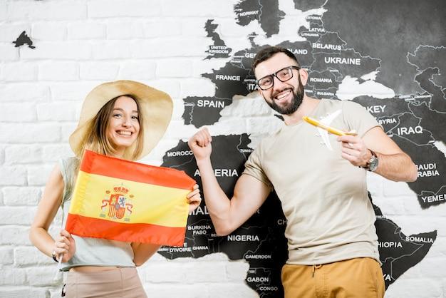 스페인의 여름 휴가를 꿈꾸며 세계 지도가 있는 벽 근처에 스페인 국기를 들고 서 있는 젊은 여행자 커플