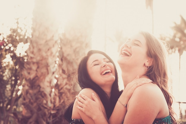 若い女性のカップルは、友情や関係、同性愛、友人のライフスタイルの中で、抱き合ったり、笑ったりして、一緒に楽しんでいます