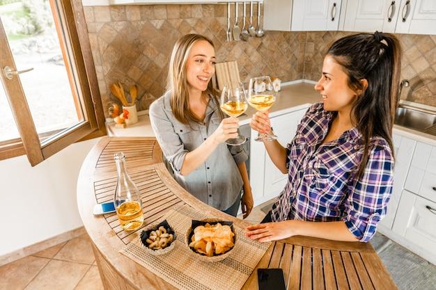 シャンパンや白ワインで祝うキッチンで家で飲んでいる若い女性の友人のカップル勉強のレッスンの代わりに食前酒を飲んで一日を楽しむためにアルコールを使用している2人の女の子