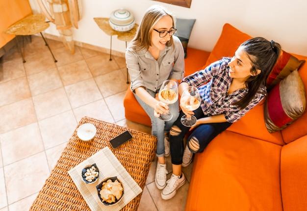 シャンパンまたは白ワインで祝うオレンジ色のソファに座って自宅で飲んでいる若い女性の友人のカップル。勉強会ではなく、お酒を使って居間で食前酒を楽しんでいる女の子