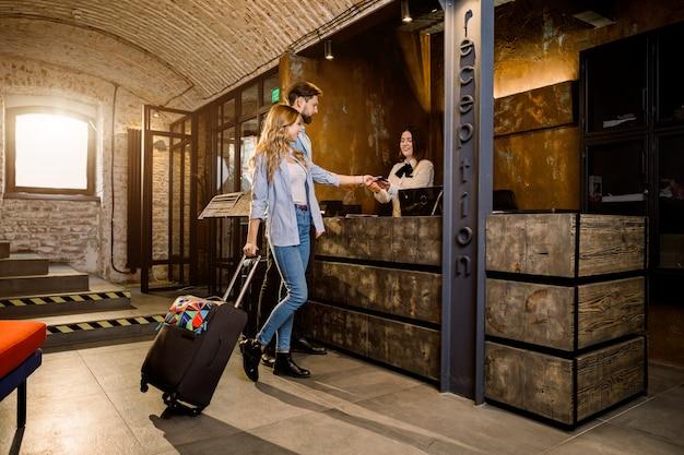 ホテルでチェックインを行う出張のカップル。ホテルのフロントデスクの近くの若いカップル