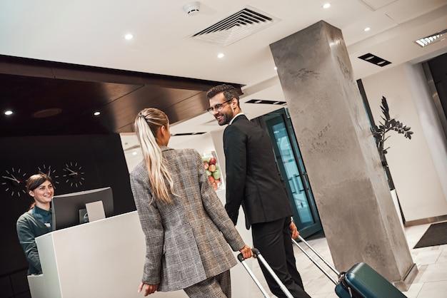 호텔에서 체크인을 하는 출장 중인 커플