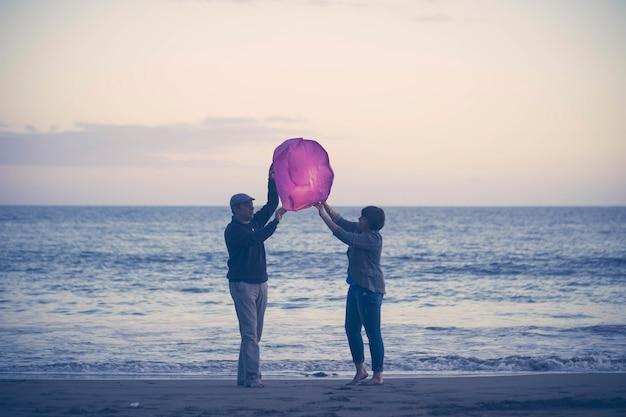 Пара на пляже, летающем бумажном фонарике. пара средних лет с китайским фонариком во время заката на пляже. радостная пара собирается выпустить бумажный фонарь в воздух на песке на живописном пляже