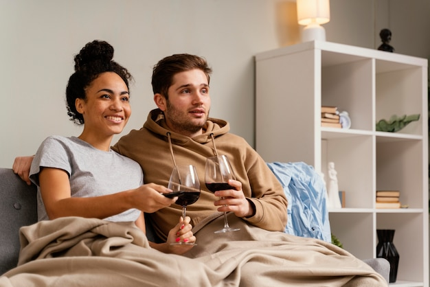 Tv를 시청하고 와인을 마시는 소파에 커플