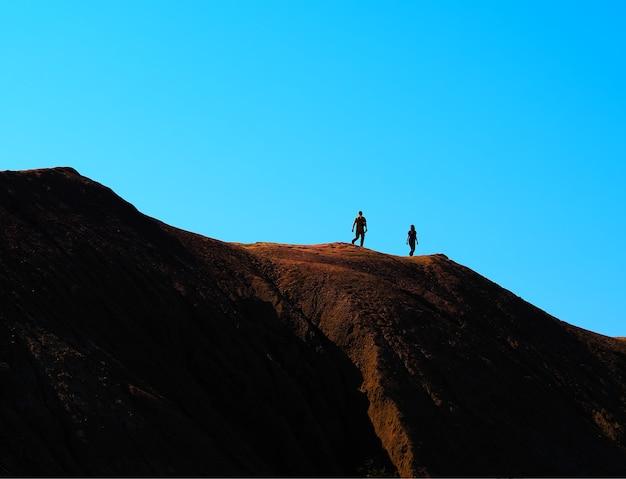 丘の山の背景にカップル