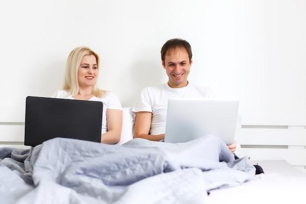 Пара на ноутбуке в постели, работает на отдельных компьютерах. молодая современная межрасовая пара, женщина, мужчина кавказской, взгляд с копией пространства.