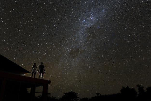 Пара на крыше, наблюдая за млики путь и звезды в ночном небе на острове бали