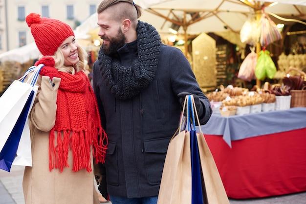 クリスマスマーケットで買い物をするカップル