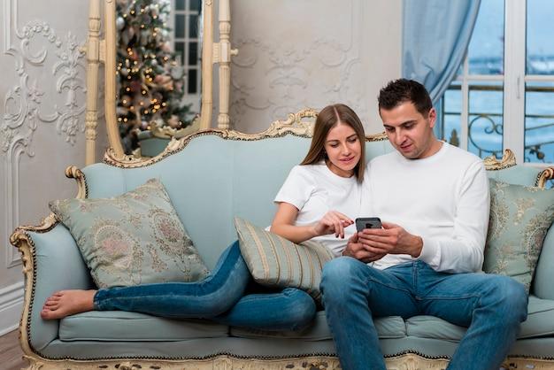 Пара на диване смотрит на смартфон