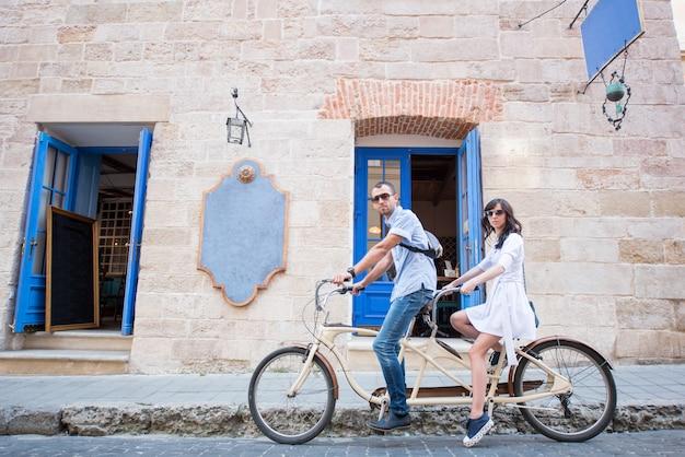 Пара на тандем велосипеде на улице города