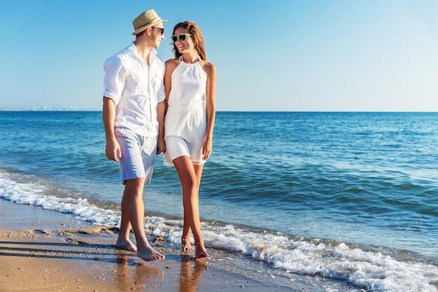 Пара на пляже гуляет и держится за руки