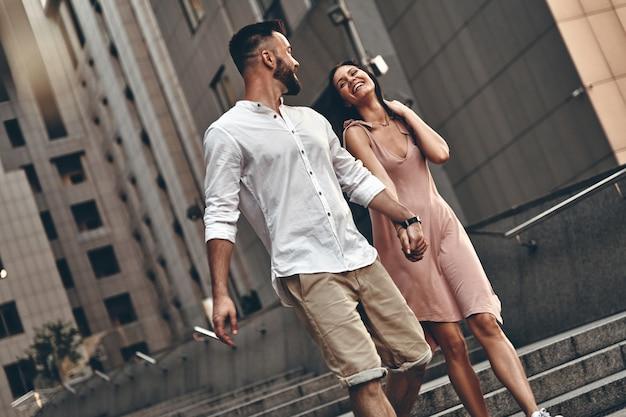 이동 중인 커플입니다. 야외에서 걷는 동안 손을 잡고 웃고 있는 아름다운 젊은 부부