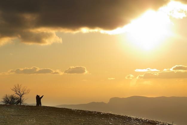 雲と空と夕日に対して丘の上のカップル