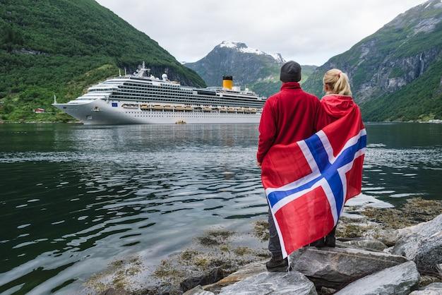 フィヨルドの岸にあるカップルがノルウェーのクルーズ船を見る