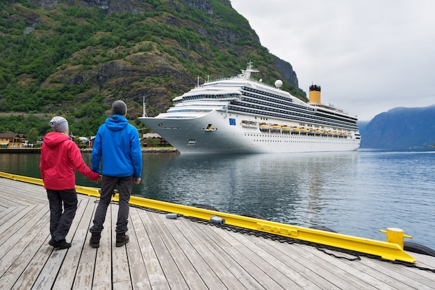 Пара на берегу фьорда смотрит на круизный лайнер, норвегия