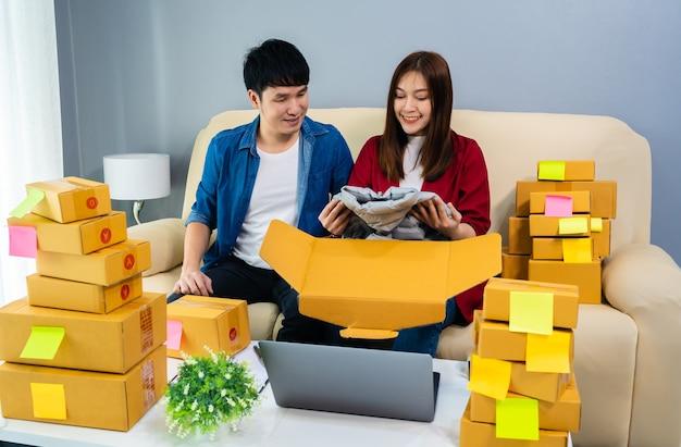 オンライン起業家がホームオフィスで小包ボックスをチェックして梱包し、顧客に配達するための製品を準備するカップル