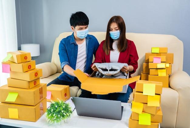 Пара онлайн-предпринимателей, упаковывающих посылку для доставки в домашний офис, люди в масках для защиты от пандемии коронавируса