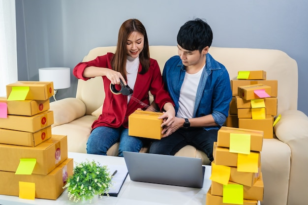 Couple online entrepreneur using tape to packing a parcel box at home office, prepare product for deliver to customer