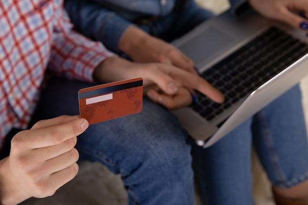 カップルのオンラインショッピングのコンセプト。手にクレジットカード。コンピューターを使う。
