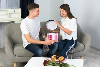 Couple opening big gift box on couch