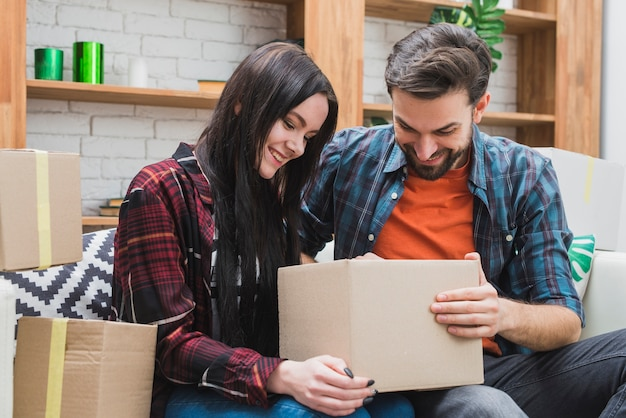 Couple opening parcel on sofa