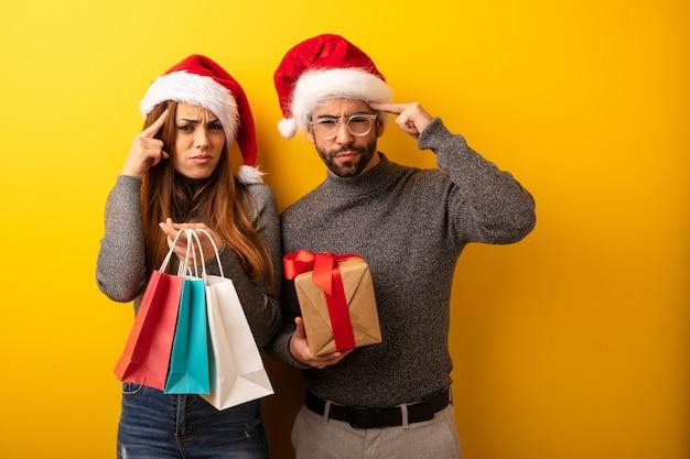 Пара или друзья, держащие подарки и сумочки, делая концентрационный жест
